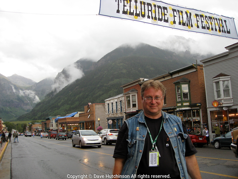 Tom Goodman, Telluride Film Festival Conversations Manager on Colorado Avenue with film festival banner, 2008.