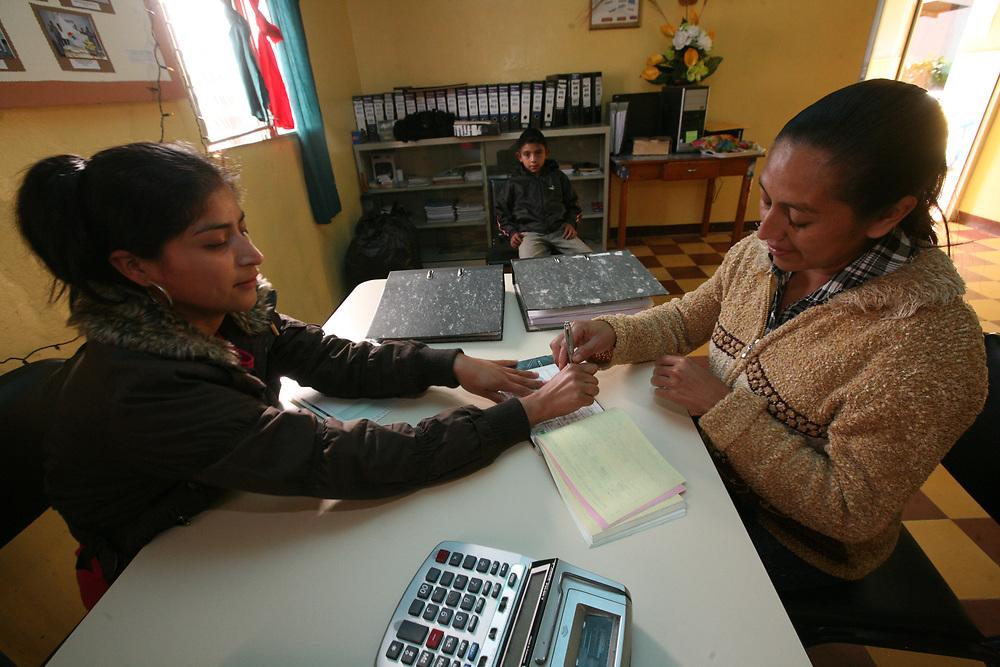 Dilcia Benítez, 23, administrative assistant at COARENE makes payment to coop member Maria Raquel Herrera Nolasco who has just delivered coffee to the coop. COARENE, Cooperativa Agropecuaria Regional Nuevo Edén, is a Fairtrade-certified coffee-producing organisation in San Juan, Intibucá, Honduras.