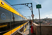 Modern electric tram part of the network of public transport in Porto, Portugal crosses the Douro River on the top of the Dom Luis I bridge a double-deck metal arch bridge that spans the River Douro between the cities of Porto and Vila Nova de Gaia in Portugal.