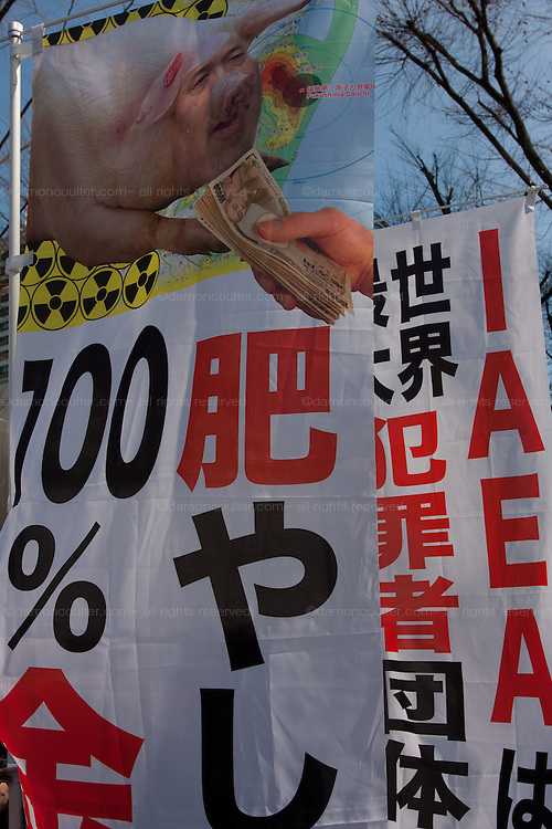 A banner portraying Minister Yukio Edano as a pig eating nuclear industry money at an anti-nuclear power demo and occupy Tokyo protest outside the Ministry of the Economy, Trade and Industry (METI) in Tokyo, Japan. Friday 27th January 2012. The protest has been running from September 2011 and was scheduled for forcible eviction by police at 5pm on January 27th as the camp had been declared a fire risk by Minister Yukio Edano, with around 500 supporters and protesters turning up to resist the eviction however the camp was still in place the night of the 27th.
