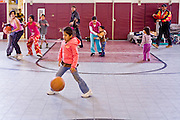 24 JANUARY 2010 -- WENDEN, AZ: Lisette Angel Montes (CQ) plays with a ball while other people from Wenden play a pick up game of basketball in the shelter in Salome. Wenden was slammed by its second 100 year flood in 10 years on Thursday night when water raced through Centennial Wash and into the small town in La Paz County west of Phoenix. Most of the town's residents were evacuated to Red Cross shelters in Salome, about 5 miles west of Wenden.    PHOTO BY JACK KURTZ
