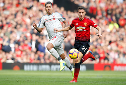 Liverpool's Roberto Firmino (left) and Manchester United's Ander Herrera battle for the ball during the Premier League match at Old Trafford, Manchester.