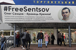 October 9, 2018 - Kiev, Ukraine - People walk past a poster with a photo of Ukrainian film director Oleg Sentsov and with the hashtag ''FreesSentsov'', displayed at the entrance to the mall in Kiev, Ukraine, on 09 October,2018. On October 5, Sentsov said that due to his critical state of health and pathological changes in the internal organs, he was planned to be force-fed, and therefore, he decided to stop the hunger strike on October 6. The 41-year-old anti-Kremlin Ukrainian film director Oleg Sentsov, who was jailed on terrorism charges, launched his hunger-strike on May 14 to demand Russia release Ukrainian political prisoners. (Credit Image: © Str/NurPhoto via ZUMA Press)