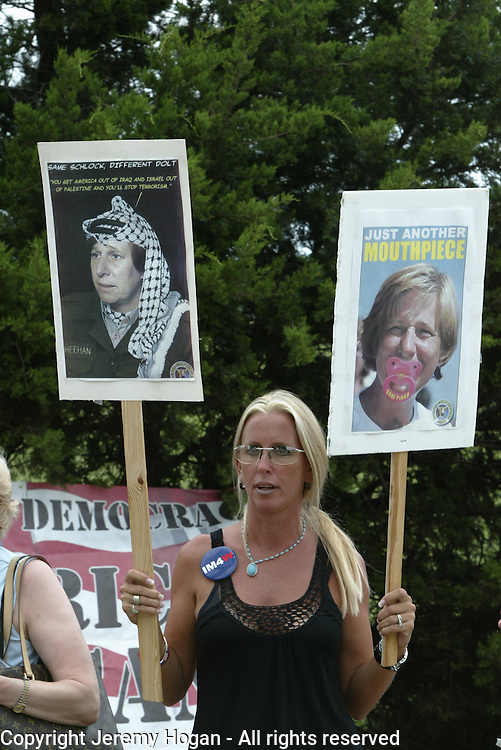 an anti Cindy Sheehan counter protester at Camp Casey I holds signs depicting Sheehan