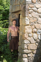 sexy man in a kilt by a stone structure