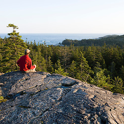 A hiker takes in the view from Duck Harbor Mountain on Isle Au Haut in Maine's Acadia National Park.