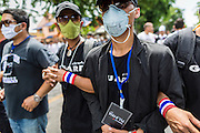 07 AUGUST 2013 - BANGKOK, THAILAND:     Anti-amnesty protesters lock arms as they march on a police position near the Parliament building in Bangkok. About 2,500 protestors opposed to an amnesty bill proposed by Thailand's ruling party marched towards the Thai parliament in the morning. The amnesty could allow exiled fugitive former Prime Minister Thaksin Shinawatra to return to Thailand. Thaksin's supporters are in favor of the bill but Thai Yellow Shirts and government opponents are against the bill. Thai police deployed about more than 10,000 riot police and closed roads around the parliament. Although protest leaders called off the protest rather than confront police, a few people were arrested for assaulting police when they tried to break through police lines. Several police officers left the scene under medical care after they collapsed in the heat.   PHOTO BY JACK KURTZ