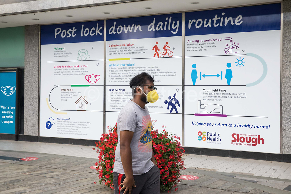A member of the public wearing a face covering walks past a COVID-19 post lockdown public information displays on 21st August 2020 in Slough, United Kingdom. Slough has been listed by Public Health England PHE and the Department for Health and Social Care DHSC as an 'area of concern' for COVID-19 following a rise in positive coronavirus cases over the last two weeks.