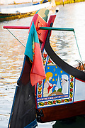 Traditional brightly painted gondola style moliceiro canal boat with saucy scene painted on prow in Aveiro, Portugal