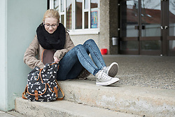 University student sitting on steps and looking for something in bag School, Bavaria, Germany