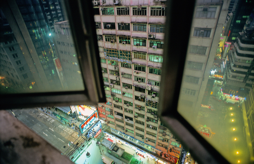 Warm air blows in through an open window on a high floor of the notorious Chungking Mansions in Hong Kong's Kowloon district.