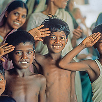 Youngsters line up for a food distribution at Mirpur Destitute Camp near , set up at an abndoned soap factory after a cyclone & bloody war of independence left millions of peole homless.  1977 image.