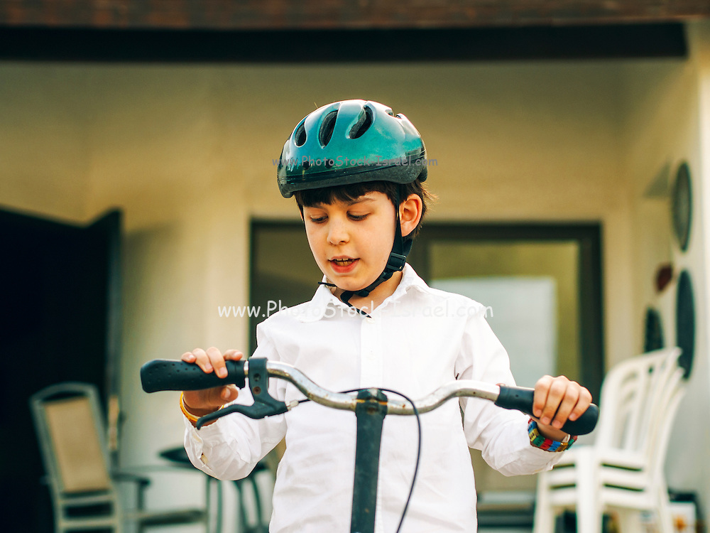 Young boy wears a helmet while riding his bicycle in the park