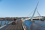 The Peace Bridge is a cycle and foot bridge across the River Foyle in Derry, Northern Ireland. It opened on 25 June 2011, connecting Ebrington Square with the rest of the city centre. It is the newest of three bridges in the city, the others being the Craigavon Bridge and the Foyle Bridge. The 235 metres (771 ft) bridge was designed by AECOM,<br /><br />The bridge was opened to the public by EU Commissioner for Regional Policy, Johannes Hahn; accompanied by the First and deputy First Ministers, Peter Robinson and Martin McGuinness; and the Irish Taoiseach Enda Kenny. It is intended to improve relations between the largely unionist 'Waterside' with the largely nationalist 'Cityside', by improving access between these areas, as part of wider regeneration plans. The bridge also provides a crossing over the railway line approaching Waterside station