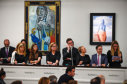 © Licensed to London News Pictures. 19/06/2019. LONDON, UK. Sales staff in front of (L to R) ''Homme À La Pipe'' by Pablo Picasso, (Est. £5,500,000 - 7,500,000) which sold for a hammer price of £6,500,000 and  ''La Magie Noire'' by René Magritte, (Est. £2,500,000 - 3,500,000) which sold for a hammer price of £3,500,000 at Sotheby's Impressionist & Modern art evening sale in New Bond Street. This is the first major evening sale to take place after Sotheby's agreed to a takeover by media and telecoms billionaire Patrick Drahi in a deal valued at $3.7bn (£2.9bn).  The big five global auction houses (Sotheby's, Christie's, Bonhams, Phillips and China Guardian Auctions) will now be held privately.  Francois Pinault, another French billionaire, owns Sotheby's traditional rival Christie's.   Photo credit: Stephen Chung/LNP