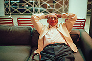 Elderly man resting on a couch with his hands behind his head in a Miami hotel lobby
