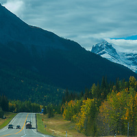 Cars drive below the Canadian Rockies on the Yellowtail Highway. Mount Roche Miette bkg.