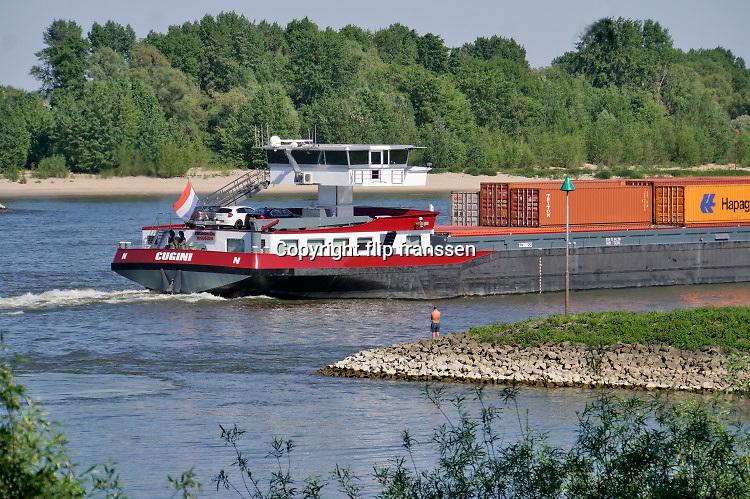 Nederland, Ooij, 21-5-2020 Terwijl mensen zich vermaken langs het water op een warme hemelvaartsdag vaart een binnenvaartschip beladen met containers voorbij . Langzaam daalt het peil van het water in de rivier. In de herfst van 2018 stond de stand bij Lobith op 6,55 meter boven nap . Die is nu nog 8,13 meter, dus nog ruim anderhalve meter hoger . Foto: Flip Franssen