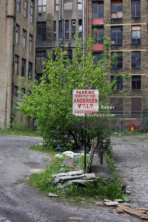 Before this land is re-devloped for new apartments, a sign urging that parking is strictly for long-gone customers and employees of a certain Anderson Mills below now derelict buildings near Bradford city centre, Yorkshire.