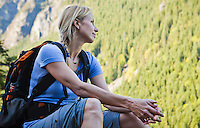 A woman hiker sitting looking up at a mountainside, Little Si Trail, Washington, USA.
