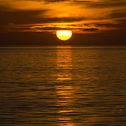 The golden sun lowers to near the horizon, creating a sharply defined reflection on the calm waters of the Great Barrier Reef. Taken at Swains Reef on the southern end of the Great Barrier Reef of the coast of Queensland, Australia.