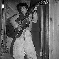 A young Chilean shows off his guitar and huaso's chaps in his family's home in Cochrane.
