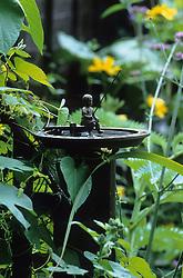 Bird bath with miniature statue of boy fishing