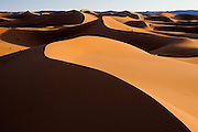 Sunset light strikes the large and expansive sand dunes of Erg Zehar, near M'hamid, Morocco.