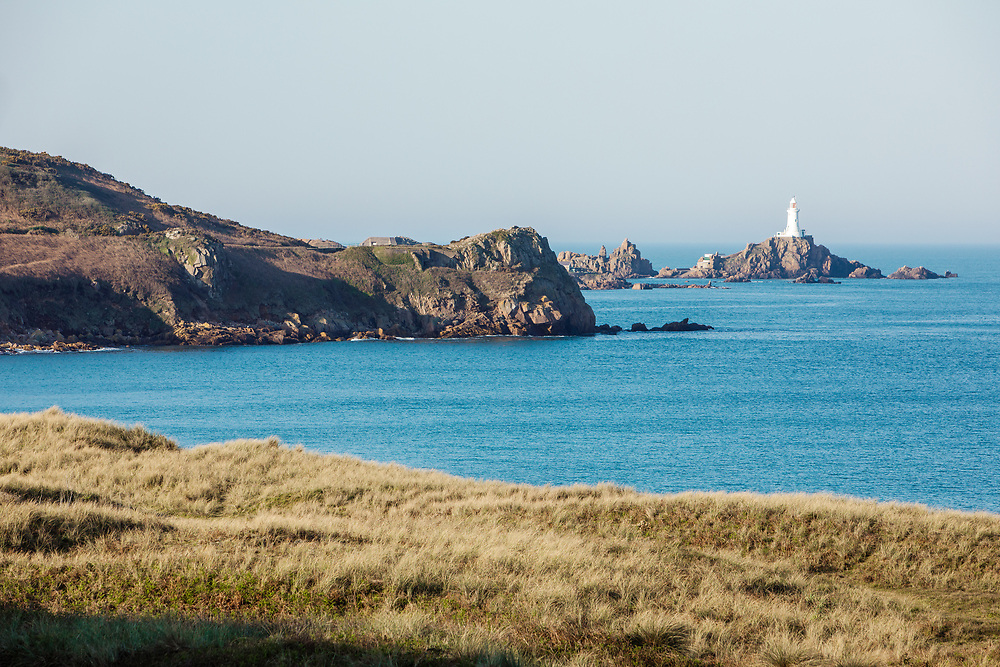 Views across the sand dunes and calm blue sea at St Ouen's Bay towards the tourist attraction, Corbiere Lighthouse in Jersey, Channel Islands