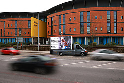 """© Licensed to London News Pictures. 05/03/2021. Salford, UK. A digital billboard showing a photograph of a nurse wearing PPE and the words """" Look them in the eyes and tell them they're only worth an extra £3.50 a week """" is seen outside Salford Royal Hospital . The British Government has proposed a one percent pay increase to nurses' salaries . Photo credit: Joel Goodman/LNP"""