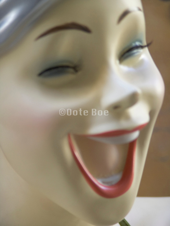 extreme close up of a display mannequin with a very big smile on her face blurry