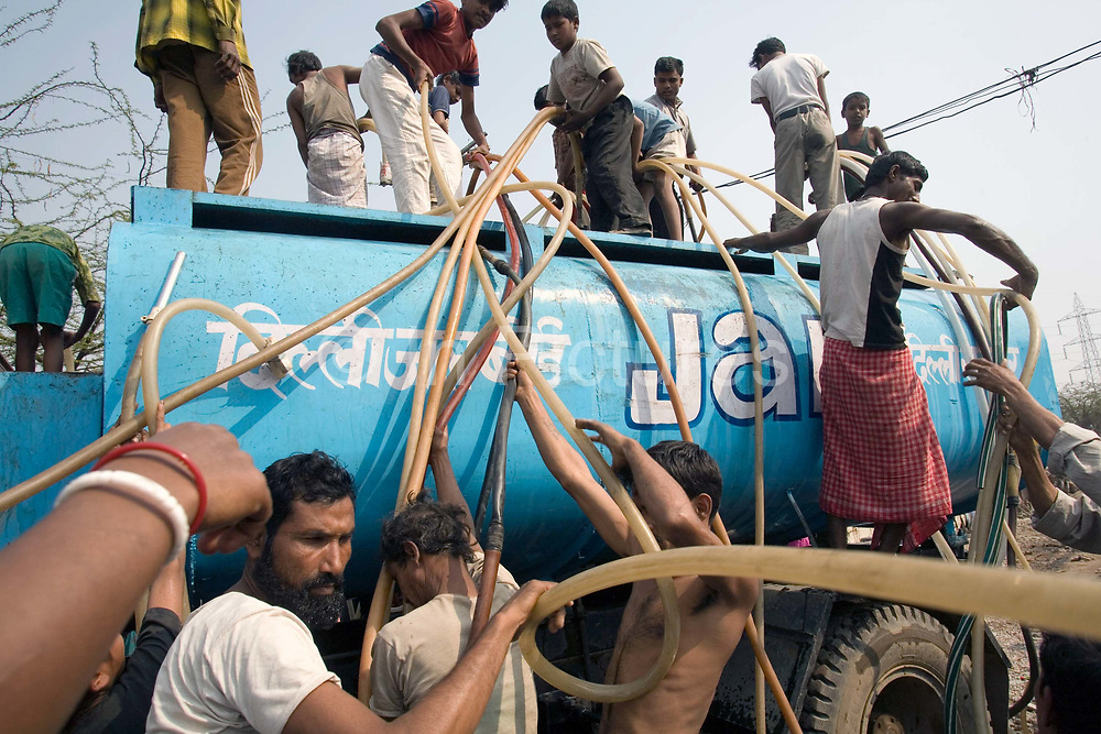 Slum dwellers scramble for water in Jai Hind Camp. The camp is home to perhaps 3000-4000 migrant workers from all over India. It has no water supplies at all so once a day, the Municipal JAL Board truck delivers some water. There is never enough for the expanding population to go around and some are left with nothing.