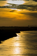 06 JUNE 2014 - IRRAWADDY DELTA,  AYEYARWADY REGION, MYANMAR: Sunrise on the Irrawaddy River in the Irrawaddy Delta (or Ayeyarwady Delta) in Myanmar. The region is Myanmar's largest rice producer, so its infrastructure of road transportation has been greatly developed during the 1990s and 2000s. Two thirds of the total arable land is under rice cultivation with a yield of about 2,000-2,500 kg per hectare. FIshing and aquaculture are also important economically. Because of the number of rivers and canals that crisscross the Delta, steamship service is widely available.   PHOTO BY JACK KURTZ