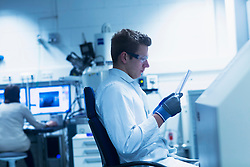 Young male scientist looking at report in an optical laboratory, Freiburg Im Breisgau, Baden-Wuerttemberg, Germany