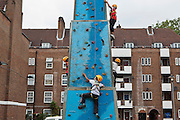 Children enjoying the climbing wall at the Pathways Project launch by Souther Housing Group, Stamford Hill Estate London. The pathways project is a voluntary information, support and guidance service aimed at young people aged 16-25 years in Hackney.