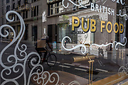 With the Coronavirus lockdown continuing into the Bank Holiday weekend, when Prime Minister Boris Johnson is due to tell the nation that only a gradual easing of regulations and social distancing rules are still to be in place, a cyclist is the only form of life seen through the window of a closed British pub in a deserted City of London, the capital's financial district, on 7th May 2020, in London, England.