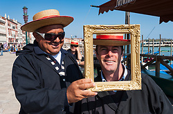 Two gondoliers having fun with picture frame in Venice Italy