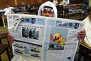 At a large coffee shop where men lounge about, smoke, and drink coffee and tea, a man reads a newspaper about the USA invasion of Iraq on March 23, 2003. Kuwait City, Kuwait. (Supporting image from the project Hungry Planet: What the World Eats.)