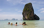 Friends cool off in the sea at Phra Nang Bay, Railay. This pure white sand beach is surrounded by spectacular limestone cliffs. Central in the bay stands Phra Nang's distinctive rock, looming over the bay dramatically.