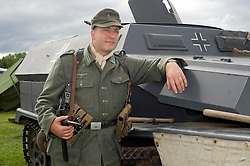 A reenactor dressed as a Panzergrenadier from the 21st Panzer Division living History group beside an SdKfz 251 Auf C(Sonderkraftfahrzeug 251) half-track  at Croft Race Circuits Nostalgia Weekend August 2010. <br /> Images © Paul David Drabble