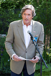 """© Licensed to London News Pictures. 19/05/2014. London, England. Pictured: Actor Nigel Havers reading war poems.  Show Garden """"No Man's Land: ABF The Soldiers' Charity Garden to mark the centenary of World War One.  Press Day at the RHS Chelsea Flower Show. On Tuesday, 20 May 2014 the flower show will open its doors to the public.  Photo credit: Bettina Strenske/LNP"""