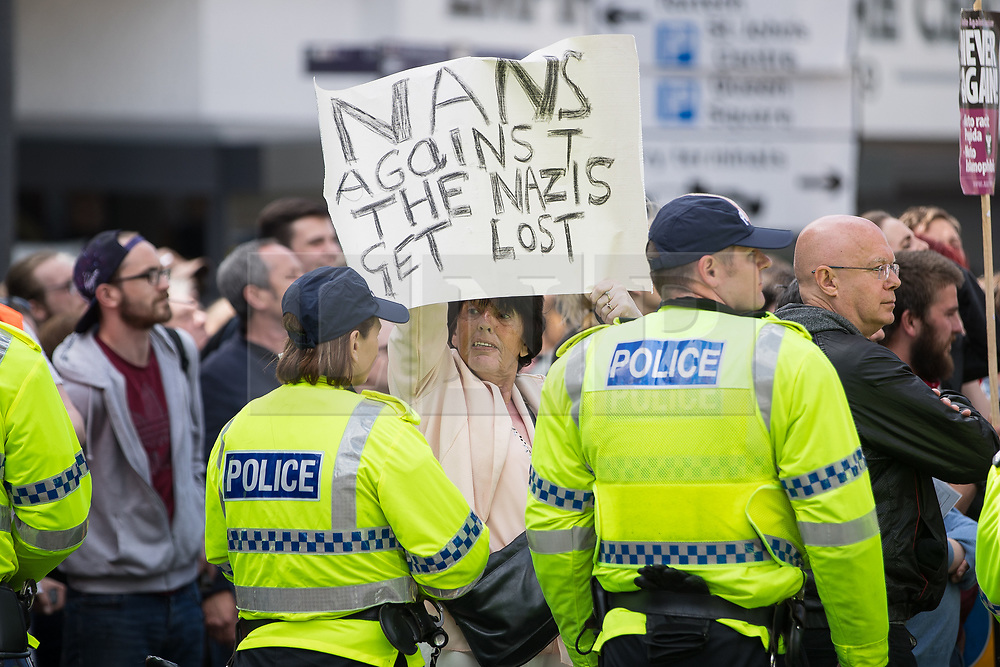 """© Licensed to London News Pictures . 03/06/2017 . Liverpool , UK . An anti fascist with a placard reading """" NANS AGAINST THE NAZIS GET LOST """" . Hundreds of police manage a demonstration by the far-right street protest movement , the English Defence League ( EDL ) and an demonstration by opposing anti-fascists , including Unite Against Fascism ( UAF ) . Photo credit: Joel Goodman/LNP"""