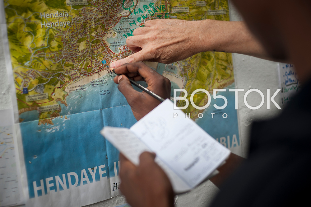 A volunteer shows some African migrants where the border is in a map in Lakaxita. Irun (Basque Country). August 15, 2018. Lakaxita is a self-managed socio-cultural space located in an occupied house, where volunteers have created a hosting network for migrants in transit who have already completed the 5-day period that can remain in public resources. This group of volunteers is avoiding a serious humanitarian problem Irún, the Basque municipality on the border with Hendaye. As the number of migrants arriving on the coasts of southern Spain incresead, more and more migrants are heading north to the border city of Irun. (Gari Garaialde / Bostok Photo)