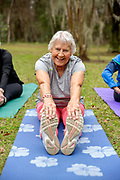 A senior woman stretching outside looking at the camera on her yoga mat.