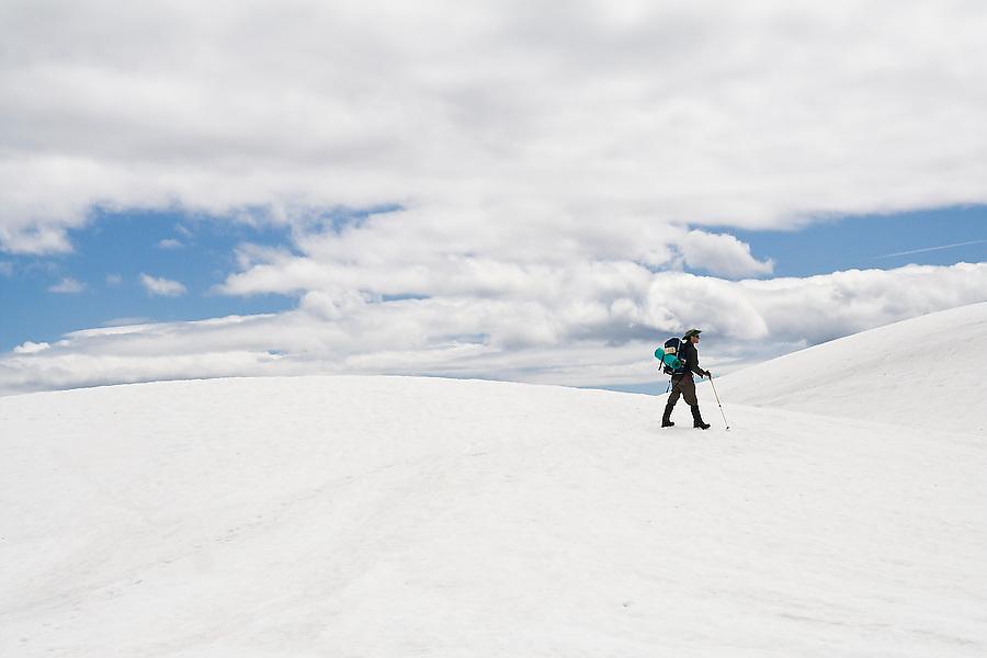 A lone male hiker walks across desolate snow covered terrain, Goat Rocks Wilderness, Washington.
