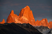 """Sunrise illuminates Cerro Fitz Roy (3405 meters or 11,171 feet elevation), seen from Mirador Condores near Los Glaciares National Park Visitor Center, in El Chalten in Santa Cruz Province, Argentina, Patagonia, South America. Monte Fitz Roy is also known as Cerro Chaltén, Cerro Fitz Roy, or Mount Fitz Roy. The first Europeans recorded as seeing Mount Fitz Roy were the Spanish explorer Antonio de Viedma and his companions, who in 1783 reached the shores of Viedma Lake. In 1877, Argentine explorer Francisco Moreno saw the mountain and named it Fitz Roy in honour of Robert FitzRoy who, as captain of HMS Beagle, had travelled up the Santa Cruz River in 1834 and charted large parts of the Patagonian coast. Mt Fitz Roy was first climbed in 1952. Cerro is a Spanish word meaning hill, while Chaltén comes from a Tehuelche word meaning """"smoking mountain"""", due to clouds that usually form around the peak."""