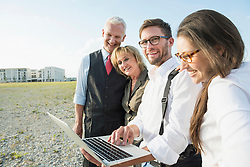 Four smiling people with laptop at development area