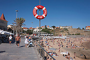 Vodafone advertising on the seafront pavement of sunbathers and walkers at Estoril near Lisbon, Portugal.