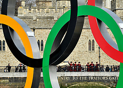 © Licensed to London News Pictures. 28/02/2012, London, UK. The Yomen of The Guard from the Tower of London line the river to watch. Giant Olympic rings measuring 11 metres high by 25 metres wide are floated down the River Thames on a barge, marking 150 days to go to the start of the London 2012 Olympic and Paralympic Games. Photo credit : Stephen Simpson/LNP
