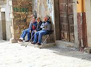 Men sitting together on stone bench, Garganta la Olla, La Vera, Extremadura, Spain